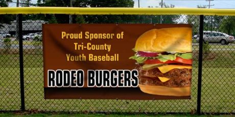 A Vinyl Banner of Rodeo Burgers on a chain link fence at a park