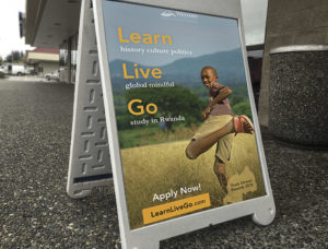 A Sandwich board of an advertisement on a sidewalk