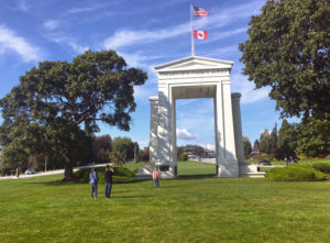 A group of people taking photos by the Peace Arch
